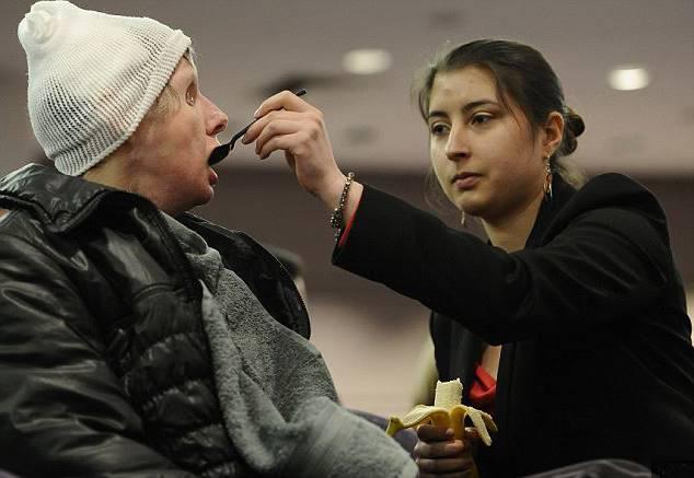 искалеченную женщину кормит девушка