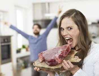 девушка кусает сырое мясо