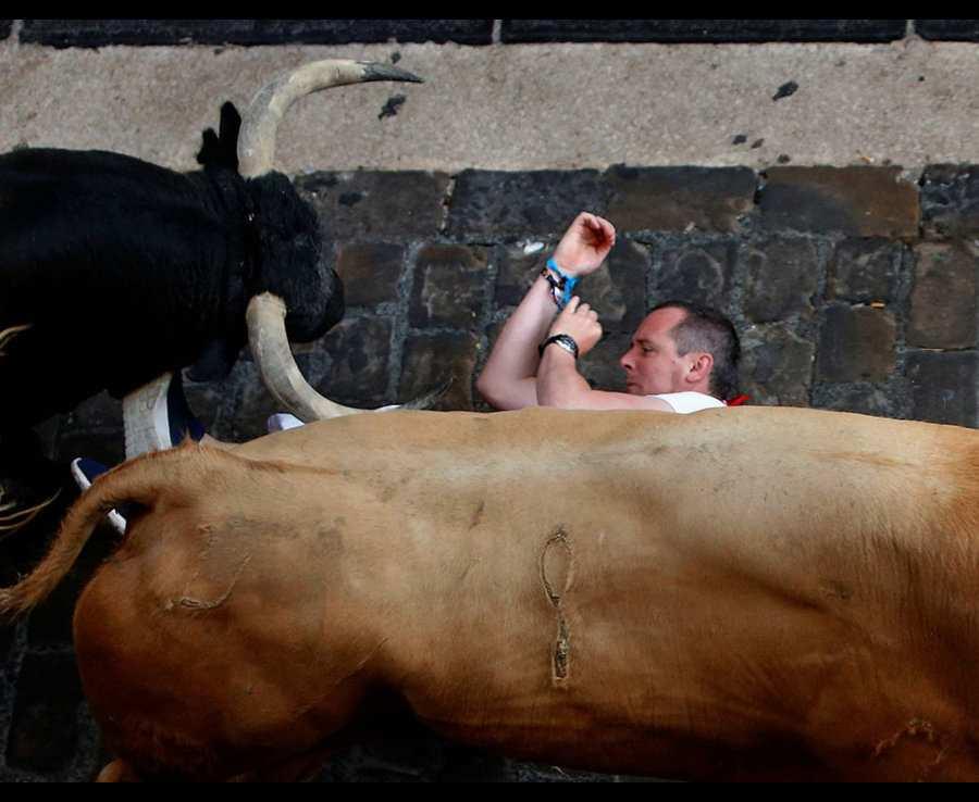 на лежащего мужчину бежит бык