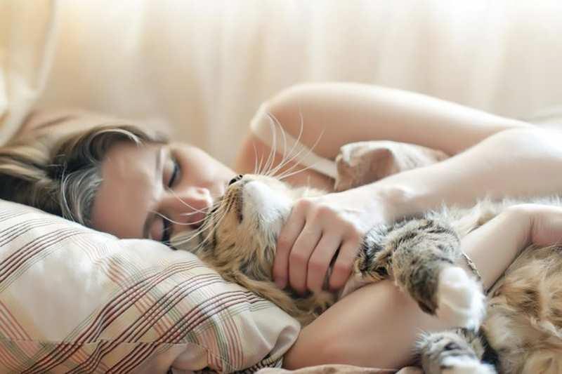 девушка обнимает совего кота в постели