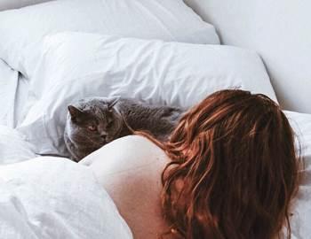 женщина спит в постели с котом